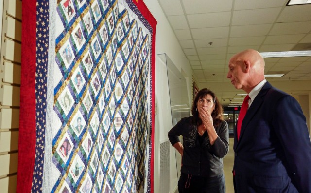 Franklin Childress, director of Army Reserve communications, and Diane Murtha, a former Marine Corps spouse, look at the photos of 9/11 victims printed across a remembrance quilt on display at the Pentagon Quilts memorial, Washington D.C., Aug. 20, 2021.