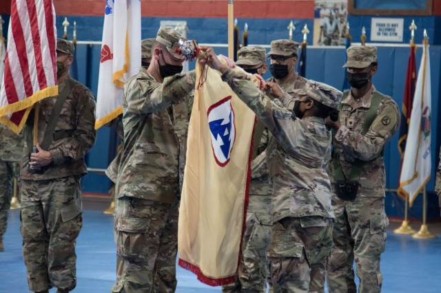 Brig. Gen. Lance G. Curtis and Command Sgt. Maj. Phelicea M. Redd, the command team for 3rd Expeditionary Sustainment Command, unfurl their unit flag at a transfer of authority ceremony at Camp Arifjan, Kuwait, on Aug. 28, 2021. The ceremony was symbolic of 3rd ESC, deployed out of Fort Bragg, North Carolina, assuming the operational command post mission for the 1st Theater Sustainment Command from the 310th Expeditionary Sustainment Command. (U.S. Army photo by Sgt. 1st Class Mary S. Katzenberger)
