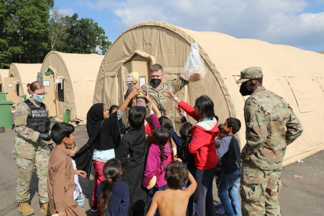 U.S. Army Soldiers from 18th Military Police Brigade and 16th Sustainment Brigade hand out bread to children in support of Operation Allies Refuge September 02, 2021 at Ramstein Air Base, Germany. Soldiers from the 21st Theater Sustainment command have assisted with providing security; food, shelter, and other basic necessities; and clean-up at the transit center on RAB - all part of preparing travelers from Afghanistan for onward movement to their final destination. (U.S. Army photo by Spc. Katelyn Myers)