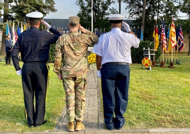 Garrison Police Chief Jason Kesselring, Garrison Command Sgt. Maj. Richard Russell and Garrison Deputy Fire Chief Rodney Millbrooks salute the wreath after placing it during the September 11th remembrance ceremony.