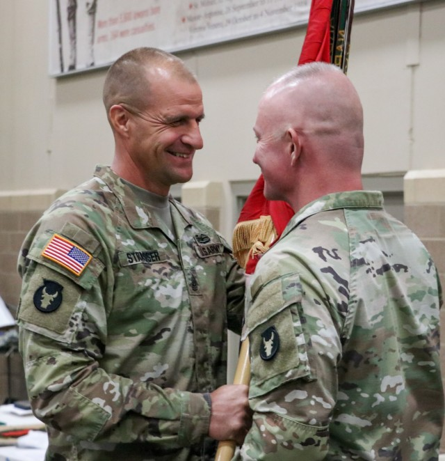 Command Sgt. Maj. Matthew Strasser, the outgoing senior enlisted leader of the 2nd Infantry Brigade Combat Team, 34th Infantry Division, Iowa Army National Guard, passes the unit colors to Col. Derek Adams, the brigade commander, during the change of responsibility ceremony for the 2nd Infantry Brigade Combat Team, 34th Infantry Division, at the Camp Dodge Joint Maneuver Training Center on Sept. 10, 2021. The ceremony was a unique event, as Matthew transferred responsibility to his younger brother, Command Sgt. Maj. Jeremy Strasser. The two brothers have dedicated a combined 47 years of service to the Red Bull brigade. (U.S. Army National Guard photo by Staff Sgt. Tawny Schmit)
