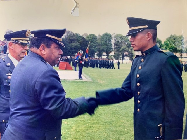 Cadet Mauricio Garcia shakes hands with the school commander during graduation from military officer school in Bogota, Colombia. Garcia, now a Chief Warrant Officer with the U.S. Army, is deployed to Tolemaida Army Base in Colombia as part of a technical advising team from U.S. Army Security Assistance Command's Fort Bragg-based training unit, the Security Assistance Training Management Organization.