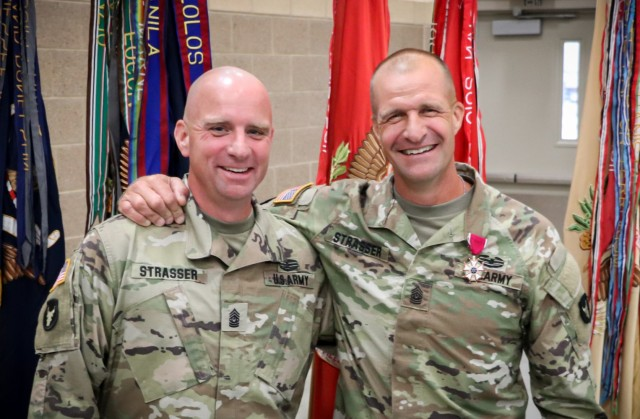 Command Sgt. Maj. Jeremy Strasser and Command Sgt. Maj. Matthew Strasser smile for a photo after the change of responsibility ceremony for the 2nd Infantry Brigade Combat Team, 34th Infantry Division, Iowa Army National Guard, at the Camp Dodge Joint Maneuver Training Center on Sept. 10, 2021. The ceremony was a unique event as Jeremy assumed responsibility from his older brother Matthew. The two brothers have dedicated a combined 47 years of service to the Red Bull brigade and have served on two deployments to together. (U.S. Army National Guard photo by Staff Sgt. Tawny Schmit)