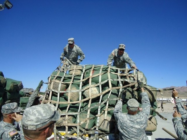 Then Sgt. Maj. Matthew Strasser and then Sgt. 1st Class Jeremy Strasser help load sandbags at Fort Irwin, Calif., before their deployment to Afghanistan in 2010. On Sept. 10, 2021, Matthew passed responsibility of the 2nd Infantry Brigade Combat Team, 34th Infantry Division, Iowa Army National Guard, to his younger brother Jeremy, marking a unique moment in Iowa National Guard history. The two brothers have dedicated a combined 47 years of service to the Red Bull brigade and have served on two deployments together. (U.S. Army National Guard photo by Staff Sgt. Tawny Schmit)