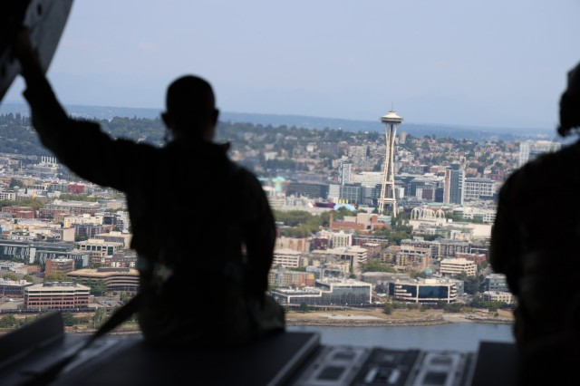 A member of the Royal Thai Army sits on the ramp of a CH-47 Chinook helicopter as it flies above Seattle, Aug. 25, 2021. The Thai Army aviators were taking part in a three-week aviation exchange with members of the Washington National Guard's 96th Aviation Troop Command. (U.S. National Guard photo by Jason Kriess)