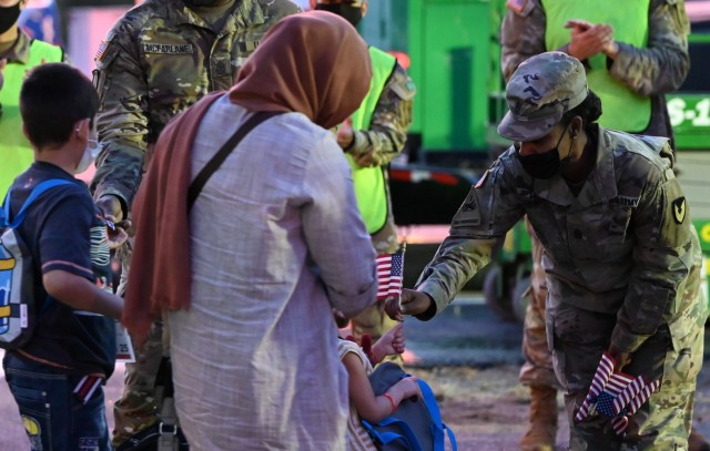 Ft. Lee Garrison Command Sgt. Maj., Command Sgt. Maj. Tamisha Love welcomes an Afghan child to Ft. Lee with a U.S. flag during reception operations, Aug. 5, 2021. The Department of Defense, through U.S. Northern Command, and in support of the Department of Homeland Security, is providing transportation, temporary housing, medical screening, and general support for up to 50,000 Afghan evacuees at suitable facilities, in permanent or temporary structures, as quickly as possible.  This initiative provides the Afghans essential support at secure locations outside Afghanistan.  (U.S. Army photo by 1st Lt. Tom Burcham IV)