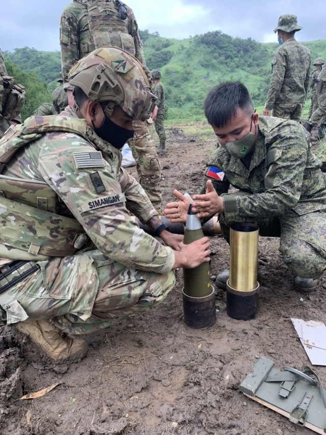 Sgt. Renchjerrybee Simangan, Logistics Advisor, Battalion Advisor Team 560, holds a 105mm round while a fuze is attached by a Soldier from the Philippine Army's 1st Brigade Combat Team, July 26, 2021 at Fort Magsaysay, Philippines during Salaknib '21.