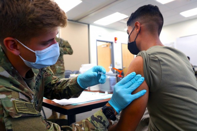 Spc. Tyler Boyer, a Hayden, Colorado native and medical specialist assigned to the 1st Stryker Brigade Combat Team, 4th  Infantry Division, administers the COVID-19 vaccine at Fort Carson, Colorado Aug 3, 2021. The 4th Inf. Div. remains committed to keeping the Fort Carson community safe and healthy by offering mobile vaccinations centers.