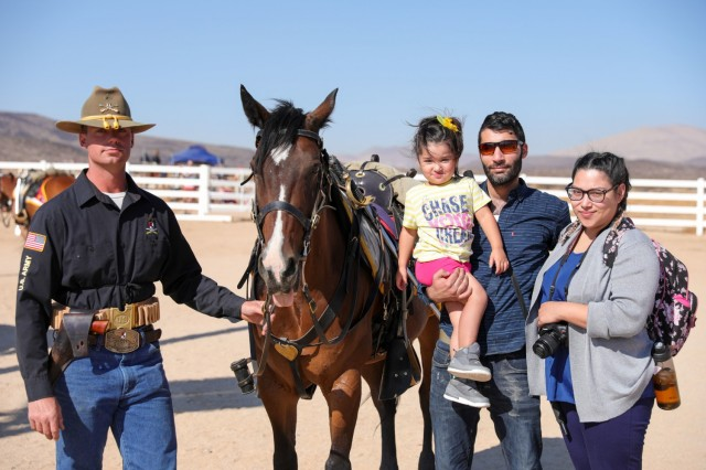 Cpl. John Wenger, Horse Detachment, Regimental Headquarters and Headquarters Troop, 11th ACR, poses with a family attending the Horse Detachment Internal Competition, Fort Irwin, Calif., August 26th, 2021. This competition prepares Troopers for the upcoming National Cavalry Competition.