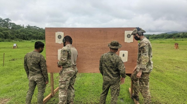 During Salaknib '21, U.S. Army Soldiers, Staff Sgt. Matthew Robinson and Sgt. Joseph Conn from Maneuver Advisor Team 5212, Force Package 21-2, discuss sight adjustments during a small arms range with the Philippine Army's 1st Brigade Combat Team, July 12, 2021 at Fort Magsaysay, Philippines.