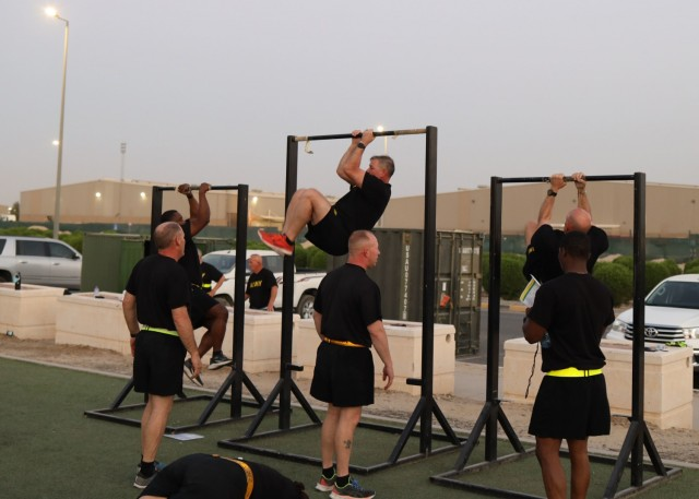 Sergeants major from across Camp Arifjan, Kuwait, competed in teams during a Sept. 12, 2021, physical fitness round-robin based on the Army Combat Physical Test, including the leg tuck shown here, along with the kettle-bell carry, the sprint, the 90-pound sled drag and the deadlift. The event was led by U.S. Army Central Command's Command Sgt. Maj. Brian A. Hester, who afterward led the sergeants major on a police call of the athletic field and the area around the camp's Zone 1 post exchange.