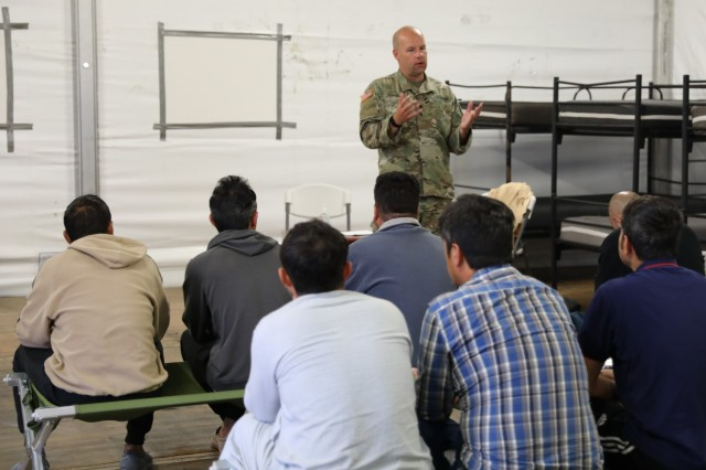 """Spc. Carl Youngblood, 457th Civil Affairs, 7th Mission Support Command, 21st Theater Sustainment Command, welcomes Afghan travelers to """"Intro to the USA"""" at Rhine Ordnance Barracks, Kaiserslautern, Germany. The cultural integration class, conducted in both Pashto and Dari, provided an introduction to life in the west, examined major differences between life in Afghanistan and life in the U.S. and encouraged participants to ask questions."""