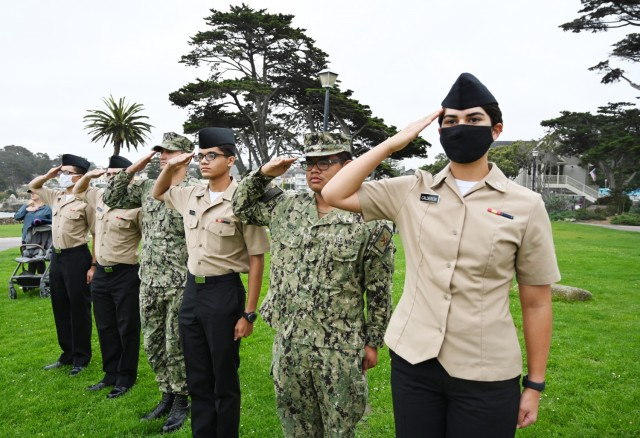 """Sailors salute for the national anthem at Lovers Point Park, Pacific Grove, Calif., Sept. 17, during the """"Afghanistan Servicemembers Memorial"""" for the 13 service members killed in action at the Kabul Airport on Aug. 26."""