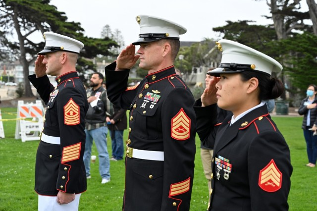 """From left, Master Gunnery Sgt. Jeffrey T. Rooke, senior enlisted leader, Marine Corps Detachment, Presidio of Monterey, Gunnery Sgt. Matthew Archbold, and Sgt. Joan Lee salute for the national anthem at Lovers Point Park, Pacific Grove, Calif., Sept. 17, during the """"Afghanistan Servicemembers Memorial"""" for the 13 service members killed in action at the Kabul Airport on Aug. 26."""