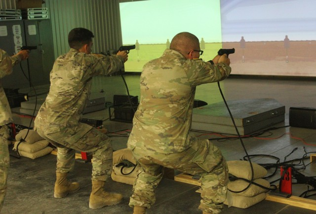 Soldiers fire from the squatting position Sept. 15, 2021, in the Engagement Skill Trainer-1 at Fort Sill, Oklahoma. The Soldiers were in training to serve as security guards augmenting Directorate of Emergency Services personnel.