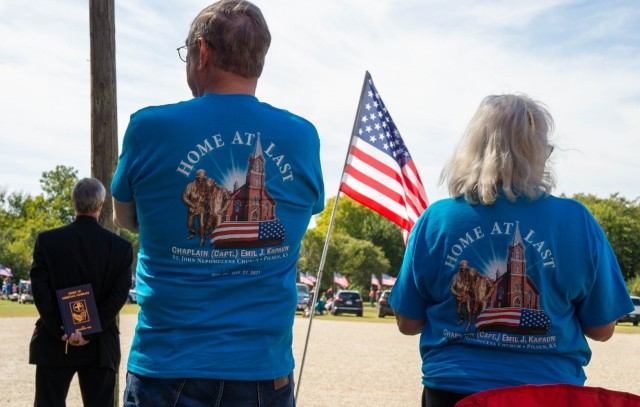 """A crowd of extended family, friends, veterans, and church members await the arrival of Chaplain (Capt.) Emil J. Kapaun, who was transported by motorcade from Wichita to Pilsen, Kan., Sept. 25, 2021. Onlookers wore blue t-shirts with the words """"Home at Last"""" printed on the back."""