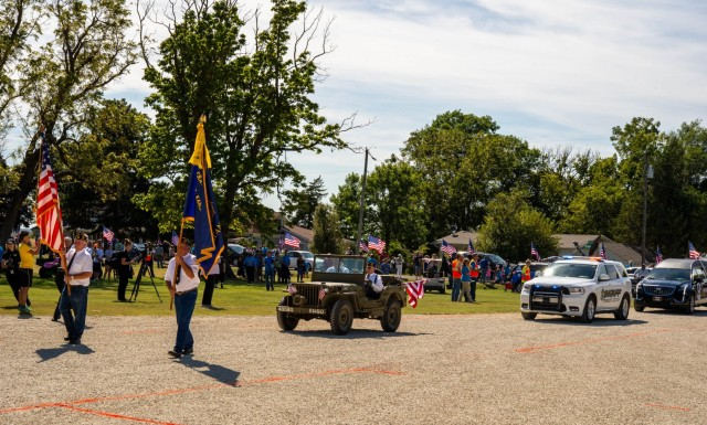 A crowd of extended family, friends, veterans, and church members witness the arrival of Chaplain (Capt.) Emil J. Kapaun, who was transported by motorcade from Wichita to Pilsen, Kan., Sept. 25, 2021. Among the long line of vehicles included a refurbished Willys M38, a green Jeep similar to the one Kapaun used to offer Holy Communion and celebrate mass while deployed in the Korean War.