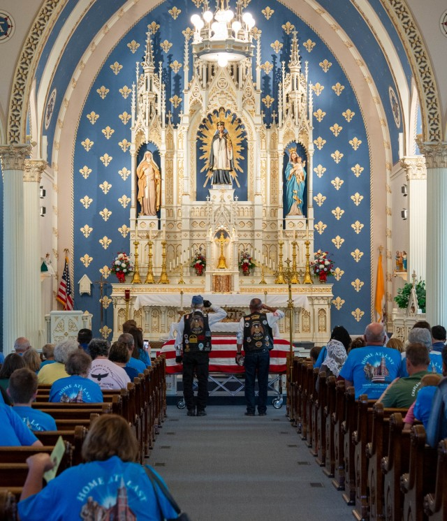 Chaplain (Capt.) Emil J. Kapaun is welcomed home with honors at the St. John Nepomucene Catholic Church in his hometown of Pilsen, Kan., Sept. 25, 2021. In the photo, two veterans with the American Legion render a final salute to Kapaun.
