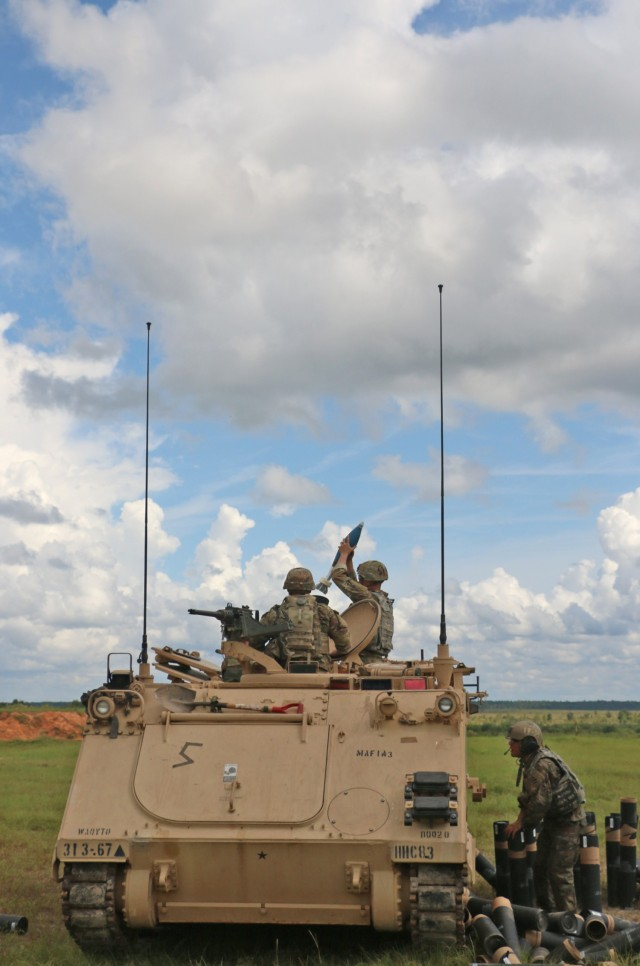 A Soldier assigned to the mortar section 3rd Battalion, 67th Armored Regiment, 2nd Armored Brigade Combat Team, 3rd Infantry Division, prepares to fire a 120mm round while his squad leader confirms direction of fire at OP4 on Fort Stewart, Georgia, Sept. 15, 2021. The mortar section in the headquarters and headquarters company must go through the mortar evaluation program, or MORTEP, in order to become certified on their weapon system for effective indirect fires in combat operations. (U.S. Army photo by Staff Sgt. Todd L. Pouliot, 50th Public Affairs Detachment)