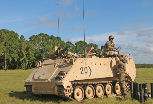 A Soldier assigned to the mortar section of 3rd Battalion, 67th Armored Regiment, 2nd Armored Brigade Combat Team, 3rd Infantry Division, hands off a 120mm round to his assistant gunner at OP4 on Fort Stewart, Georgia, Sept. 15, 2021. The mortar section in the headquarters and headquarters company must go through the mortar evaluation program, or MORTEP, in order to become certified on their weapon system for effective indirect fires in combat operations. (U.S. Army photo by Staff Sgt. Todd L. Pouliot, 50th Public Affairs Detachment)
