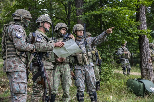 Romanian Soldiers assigned to Bulldog Company, 812 Infantry Battalion, discuss target acquisition during Saber Junction 21, Sept. 19, 2021, in Hohenfels Training Area, Germany. Saber Junction is a 7th Army Training Command-conducted, U.S. Army Europe and Africa-directed combat training rotation designed to assess the readiness and execution of unified land operations in a joint combined environment, and to promote interoperability with participating allied and partner nations.