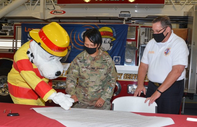 """Sparky the Fire Dog gets help from Garrison Commander Col. Karin L. Watson as he places his official """"paw stamp"""" on the 2021 Fire Prevention Week Proclamation during a signing ceremony Monday in Fort Lee Fire Station 2. Also pictured is Fort Lee Fire Chief Phil Wilkinson. (U.S. Army photo by Patrick Buffett)"""