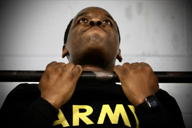 Army Reserve Sgt. Demos Moore, a chemical, biological, radiological and nuclear specialist assigned to the 377th Chemical Company, 485th Chemical Battalion, 76th Operational Response Command, performs a series of pull-ups at a gym in Richmond, Virginia, February 18. Moore, who once struggled with being overweight and out of shape has dedicated himself to physical fitness, losing more than forty-pounds in the past four months. (Official U.S. Army Reserve photo by Sgt. 1st Class Brent C. Powell)