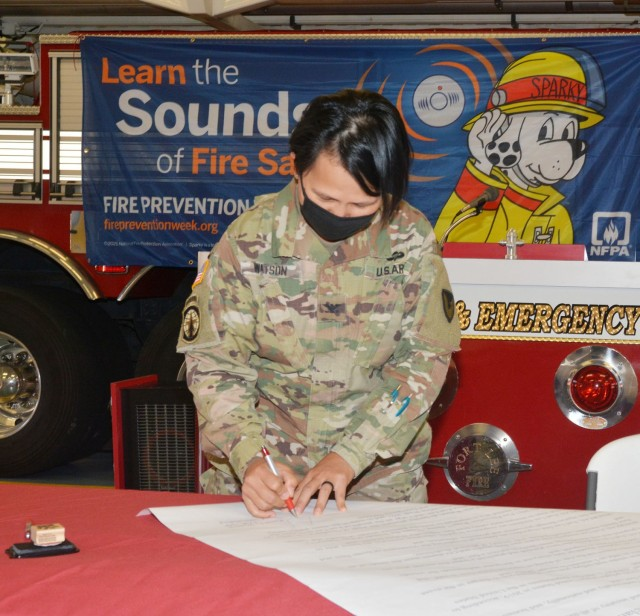 """Garrison Commander Col. Karin L. Watson places her signature on the 2021 Fire Prevention Week Proclamation during a signing ceremony Monday in an open bay of Fire Station 2. An opening line of the document read, """"Fire is a serious public safety concern both locally and nationally, and homes are the locations where people are at greatest risk from fire."""" The FPW observance is set for Oct. 3-9. (U.S. Army photo by Patrick Buffett)"""