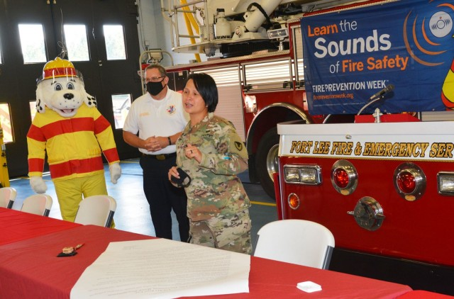 """Garrison Commander Col. Karin L. Watson offers her """"heartfelt thanks"""" to the numerous firefighters assembled for Fire Protection Week proclamation signing ceremony that took place Monday in an open bay of Fire Station 2. Watson acknowledged the professionalism of Fort Lee's first responders and their dedication to """"protecting the community day and night, 365 days a year."""" (U.S. Army photo by Patrick Buffett)"""