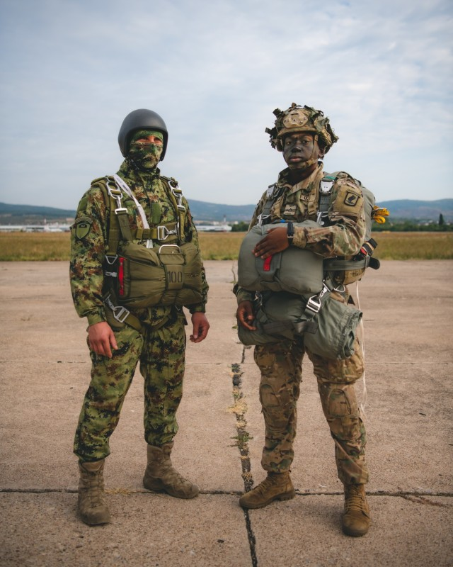 A U.S. Army paratrooper assigned to the 54th Brigade Engineer Battalion (Airborne) stands with a Serbian special operations paratrooper from the 63rd Parachute Brigade for a photo before a joint airborne operation as part of Exercise Skybridge 21 at the Medja Training Area in Niš, Serbia on Sept. 16, 2021.  Skybridge 21 is a bi-lateral training exercise taking place in Serbia from Sept. 13 - 17, 2021. Paratroopers of both the 54th Brigade Engineer Battalion (Airborne), 173rd Airborne Brigade and the 63rd Parachute Brigade, Serbian Armed Forces are working alongside supporting components in order to conduct a joint force airborne operation with a training aerial humanitarian aid package delivery. This exercise enhances the interoperability of allied and partner nations by demonstrating the unit's ability to readily respond to any crisis.  The 173d Airborne Brigade is the U.S. Army's Contingency Response Force in Europe, providing rapidly deployable forces to the United States European, Africa and Central Command areas of responsibility. Forward deployed across Italy and Germany, the brigade routinely trains alongside NATO allies and partners to build partnerships and strengthen the alliance.