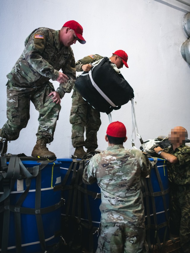 U.S. Army Parachute Riggers assigned to the 5th Quartermaster Theater Aerial Delivery Company brief Special Operations Paratroopers from the 63rd Parachute Brigade, Serbian Armed Forces on the rigging and functions of the cargo delivery system on a training humanitarian aid package. These cargo drops will be delivered in conjunction with a joint force airborne operation to be conducted by the 54th Brigade Engineer Battalion (Airborne) and the 63rd Parachute Brigade in the coming days of the exercise. This training is part of Exercise Skybridge 21 in the Medja Training Area in Niš, Serbia on Sept. 14, 2021.  Skybridge 21 is a bi-lateral training exercise taking place in Serbia from Sept. 13 - 17, 2021.  Paratroopers of both the 54th Brigade Engineer Battalion (Airborne), 173rd Airborne Brigade and the 63rd Parachute Brigade, Serbian Armed Forces are working alongside supporting components in order to conduct a joint force airborne operation with a training aerial humanitarian aid package delivery. This exercise enhances the interoperability of allied and partner nations by demonstrating the unit's ability to readily respond to any crisis.  The 173d Airborne Brigade is the U.S. Army's Contingency Response Force in Europe, providing rapidly deployable forces to the United States European, Africa and Central Command areas of responsibility. Forward deployed across Italy and Germany, the brigade routinely trains alongside NATO allies and partners to build partnerships and strengthen the alliance.