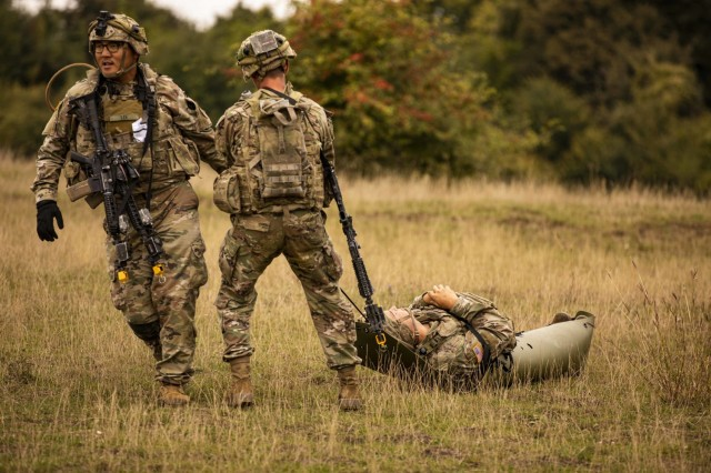 """U.S. Army Soldiers assigned to Alpha Company, 1st Battalion, 16th Infantry Regiment """"Iron Rangers,"""" 1st Armored Brigade Combat Team, 1st Infantry Division, move a simulated casualty during a multinational situational training exercise in Cincu, Romania, Sept. 22, 2021. The training incorporated Soldiers from Poland, Romania and Portugal, and enhanced the interoperability between the NATO allies."""
