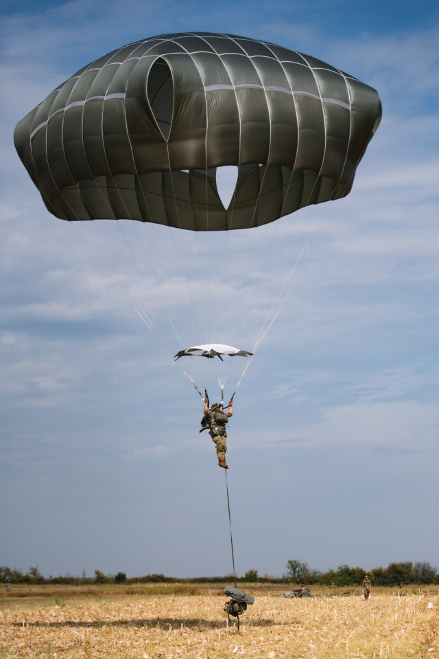 A U.S. Army paratrooper assigned to the 54th Brigade Engineer Battalion (Airborne) conducts a joint airborne operation with Serbian special operations paratroopers from the 63rd Parachute Brigade as part of Exercise Skybridge 21 at the Medja Training Area in Niš, Serbia on Sept. 16, 2021.  Skybridge 21 is a bi-lateral training exercise taking place in Serbia from Sept. 13 - 17, 2021. Paratroopers of both the 54th Brigade Engineer Battalion (Airborne), 173rd Airborne Brigade and the 63rd Parachute Brigade, Serbian Armed Forces are working alongside supporting components in order to conduct a joint force airborne operation with a training aerial humanitarian aid package delivery. This exercise enhances the interoperability of allied and partner nations by demonstrating the unit's ability to readily respond to any crisis.  The 173d Airborne Brigade is the U.S. Army's Contingency Response Force in Europe, providing rapidly deployable forces to the United States European, Africa and Central Command areas of responsibility. Forward deployed across Italy and Germany, the brigade routinely trains alongside NATO allies and partners to build partnerships and strengthen the alliance.