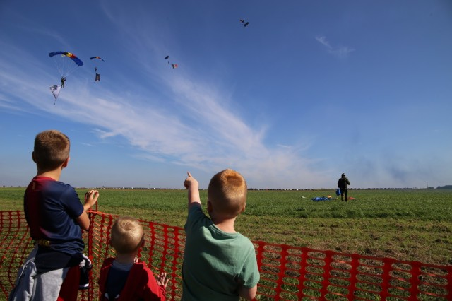 Spectators watch Belgian paratroopers land on Chièvres Air Field. Chièvres Air Fest took place Sept. 25, 2021 at Chièvres Air Base, Belgium. The Saturday event was the first time the base was opened to the general public in more than 25 years. (U.S. Army photo by Libby Weiler, USAG Benelux Public Affairs)