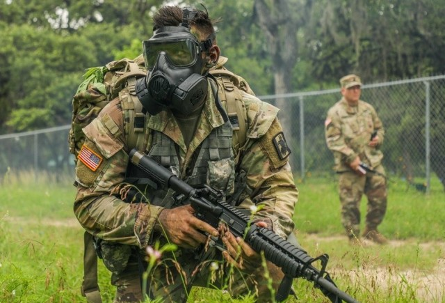 Spc. Justin Earnhart, assigned to the 470th Military Intelligence Brigade, pulls security while wearing a joint service general purpose mask during an exercise in the Army Futures Command's Best Warrior Competition on Fort Sam Houston, Texas, June 9, 2021. The Best Warrior Competition evaluates a Soldier's physical ability, tactical performance and knowledge of Army regulations. Twenty-four finalists representing 12 Army commands will complete in person at the Army-level competition to determine the service's top Soldier and noncommissioned officer.