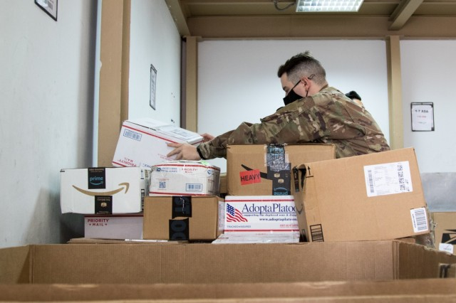 Cpl. Brett D. Ellis, a human resources specialist assigned to the Fort Bragg, North Carolina, based Headquarters and Headquarters Company, 3rd Expeditionary Sustainment Command, stacks parcels bound for Soldiers at his unit at the post office on Camp Arifjan, Kuwait, on Oct. 2, 2021. Ellis, a native of Fort Worth, Texas, is one of many Soldiers who deployed to Kuwait in August to staff the 1st Theater Sustainment Command Operational Command Post. (U.S. Army photo by Sgt. 1st Class Mary S. Katzenberger)