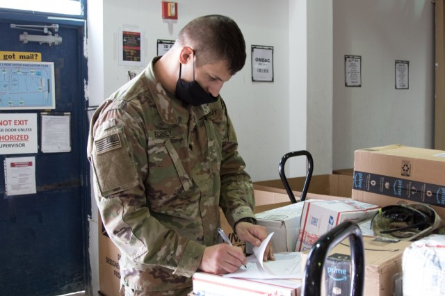 Spc. Joby L. Forney, a chemical, biological, radiological and nuclear specialist assigned to the Fort Bragg, North Carolina, based Headquarters and Headquarters Company, 3rd Expeditionary Sustainment Command, signs documents at the post office on Camp Arifjan, Kuwait, on Oct. 2, 2021. Forney, a native of Bend, Ore., is one of many Soldiers who deployed to Kuwait in August to staff the 1st Theater Sustainment Command Operational Command Post.