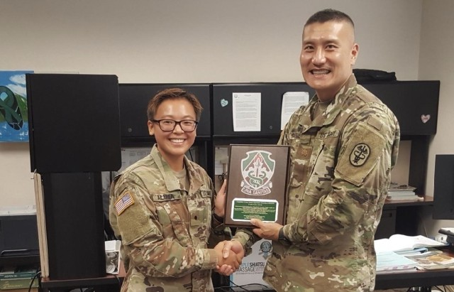 Cadet Loise Aleria, left, a member of Army ROTC at Furman University, Greenville, S.C.,  is presented a farewell plaque by Maj. Seo Yatsushiro, officer in charge, Public Health Activity-Fort Lewis, Joint Base Lewis-McChord, Wash., July 19, 2021. Aleria participated in a three-week U.S. Army Medical Internship Program where she was exposed to a variety of specialties in medical logistics and preventive medicine. (Courtesy Photo)