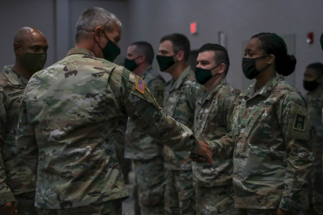 """Chief Warrant Officer 3 Quintamaria Weeks, a Soldier assigned to 188th Infantry Brigade, receives a challenge coin from Maj. Gen. Charles D. Costanza, commander of the 3rd Infantry Division, Oct. 6, 2021, on Fort Stewart, Georgia, for her support to the division during Warfighter 22-1. The First Army's 188th Combined Arms Training Brigade at Fort Stewart, whose mission is to support pre-mobilization training of Army National Guard and Reserve units, provided experienced Soldiers as Observer, Coach, Trainers to enhance the experience for the 3rd ID training audience, guiding and advising the staff and its leaders throughout the """"fight."""""""