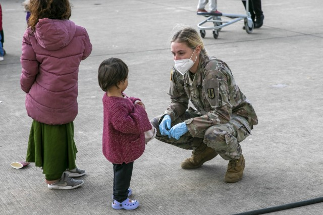 Spc. Sophia Harmelink, a Multiple Launch Rocket System Crewmember assigned to 1st Battalion, 77th Field Artillery Regiment, plays with a little Afghan girl on Sept. 30, 2021  at Ramstein Air Base, Germany. Approximately 175 Soldiers from 1-77 FAR, 41st Field Artillery Brigade have been assigned to support Operation Allies Welcome and augment the security force at the holding facilities at Ramstein providing life support for Afghan travelers awaiting follow on flights. (Official U.S. Army photo by Spc. Ryan Barnes)