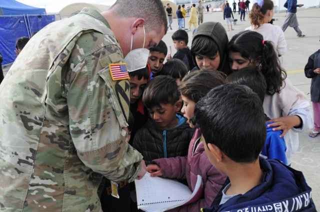 Cpt. Micah Thompson, the commander for Alpha Battery, 1st Battalion, 77th Field Artillery Regiment, quizzes the Afghan students on their numbers as they wait to enter the enter the temporary school house at Ramstein Air Base, Germany on Sept. 30, 2021. Approximately 175 Soldiers from 1-77 FAR, 41st Field Artillery Brigade have been assigned to support Operation Allies Welcome and augment the security force at the holding facilities at Ramstein providing life support for Afghan travelers awaiting follow on flights. (Official U.S. Army photo by Maj. Joe Bush)
