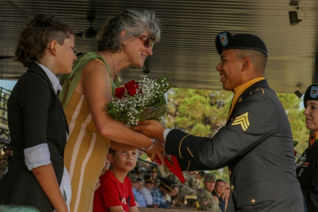 Mrs. Denise Carozza, wife of 1st Cavalry Division Sustainment Brigade outgoing commander, Col. Steven N. Carozza, receives a bouquet of red roses that symbolize the bonds of loyalty and affection from the command during a change of command ceremony at Fort Hood's Cooper Field, August 9, 2019. (U.S. Army Photo by Sgt. 1st Class Ashleigh E. Martinez)