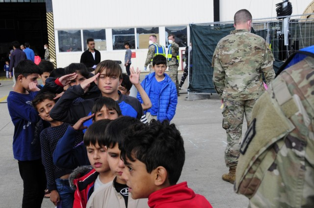 A young Afghan boy renders a proper military salute to the Soldiers assigned to 1st Battalion, 77th Field Artillery Regiment, while waiting in line to enter the temporary school house at Ramstein Air Base, Germany on Sept. 30, 2021. Approximately 175 Soldiers from 1-77 FAR, 41st Field Artillery Brigade have been assigned to support Operation Allies Welcome and augment the security force at the holding facilities at Ramstein providing life support for Afghan travelers awaiting follow on flights. (Official U.S. Army photo by Maj. Joe Bush)