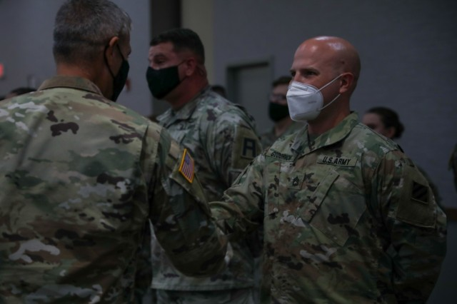 Sgt. 1st Class Gregory Goodrich, a plans and operations noncommissioned officer assigned to Headquarters and Headquarters Battalion, 3rd Infantry Division, receives a challenge coin from Maj. Gen. Charles D. Costanza, commanding general of the division, Oct. 6, 2021, on Fort Stewart, Georgia, for his success as the main command post battle NCO during Warfighter 22-1. The 3rd ID served as a subordinate unit in the V Corps' certifying WFX 22-1 and leveraged the training to develop new processes, integrate new techniques of warfighting, and begin solving future warfighting challenges now.