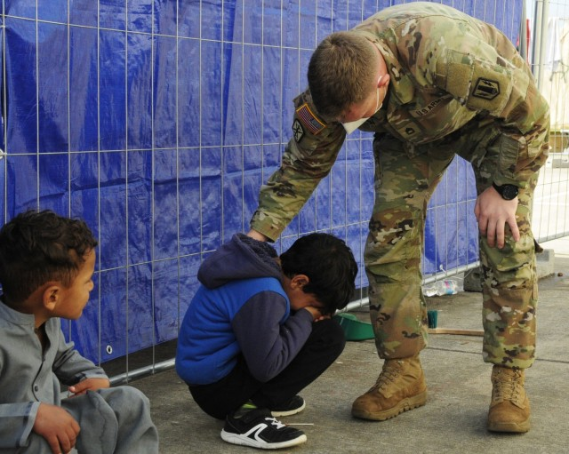 Sgt. First Class Robinson, a platoon sergeant assigned to 1st Battalion, 77th Field Artillery Regiment, stops to consoles an Afghan child at Ramstein Air Base, Germany while checking up on his Soldiers conducting gate guard in the facilities on Sept. 30, 2021. Approximately 175 Soldiers from 1-77 FAR, 41st Field Artillery Brigade have been assigned to support Operation Allies Welcome and augment the security force at the holding facilities at Ramstein providing life support for Afghan travelers awaiting follow on flights. (Official U.S. Army photo by Maj. Joe Bush)