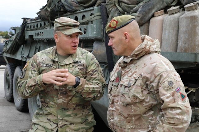 Warrant Officer Steven Mulhearn (right), Command Sgt. Maj. of the 1st Armoured Infantry Brigade (UK), and Command Sgt. Maj. Benjamin Pingel of the 2nd Cavalry Regiment, talk about the similarities and differences of their units at a static display on Rose Barracks, Germany. The 1st Armoured Infantry Brigade visited the 2d Cavalry Regiment to discuss capabilities and future training opportunities between the two units Oct. 5, 2021.