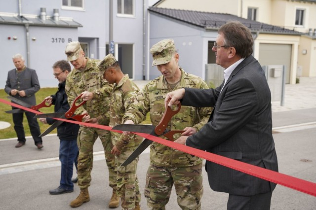 From left to right, Mr. Roman Beer, Col. Christopher Danbeck, Command Sgt. Maj. Sebastian Camacho, Col. Patrick Dagon, and Vilseck Mayor Hans-Martin Schertl cut a ribbon to signify the completion of 15 newly constructed homes at Rose Barracks, Oct. 6, 2021. (U.S. Army photo by Julian Temblador)