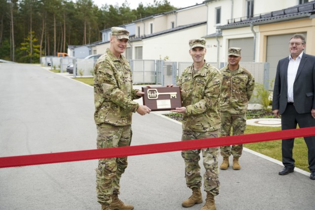 Col. Patrick Dagon (right), the U.S. Army Corps of Engineers Europe District commander, presents U. S. Army Garrison Bavaria Garrison Command Col. Christopher Danbeck with a symbolic key to the neighborhood during a ribbon-cutting ceremony at Rose Barracks on Oct. 6, 2021. (U.S. Army photo by Julian Temblador)