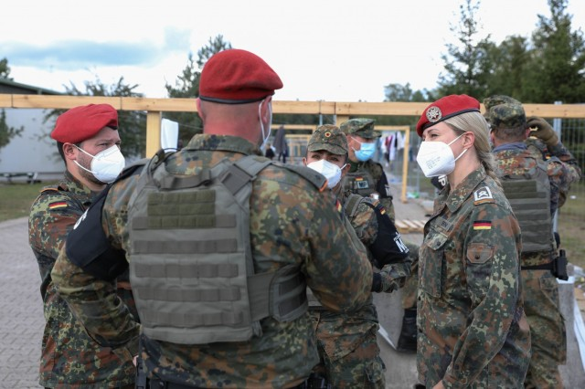 German Bundeswehr Master Sgt. Sandra Born (right) with Liaison Detachment BwLOGCOM, 21st Theater Sustainment Command, discusses plans for Operation Allies Welcome at Rhine Ordnance Barracks in Kaiserslautern, Germany, Sept. 30, 2021. The German Armed Forces have worked side by side with the 18th Military Police Brigade, 902nd Engineer Company from Grafenwöhr, 92nd MP Company from Kaiserslautern, the 529th and 571st MP companies out of Wiesbaden, 527th MP Company out of Hohenfels and Soldiers from Kronos Troop, 2nd Cavalry Regiment. (U.S. Army photo by Spc. Katelyn Myers)