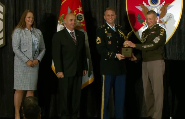 Sgt. Maj. of the Army Michael A. Grinston, right, presents the Sgt. Maj. Larry L. Strickland Educational Leadership Award to Sgt. 1st Class Brandon Johnson, second from right, assigned to the 11th Missile Defense Battery, 10th Army Air and Missile Defense Command, during the Sergeant Major of the Army Forum and Awards Ceremony in Washington, D.C., Oct. 11, 2021.